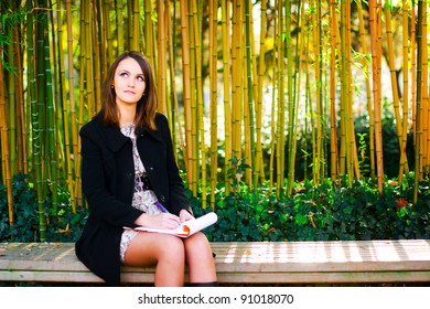 Young european girl in a black topcoat