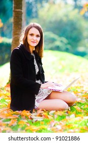 Young european girl in a black topcoat sitting on the grass with a white laptop on autumn background