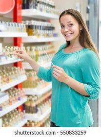 Young european girl chooses perfume in the shop