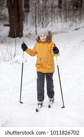 Young European girl cross-country skiing in winter snowy forest, full-length