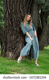 young European girl, natural appearance, long hair, beautiful face, green linen light jumpsuit. Beads on neck. Originally pose for full height in city park near trees. linen womens clothing.