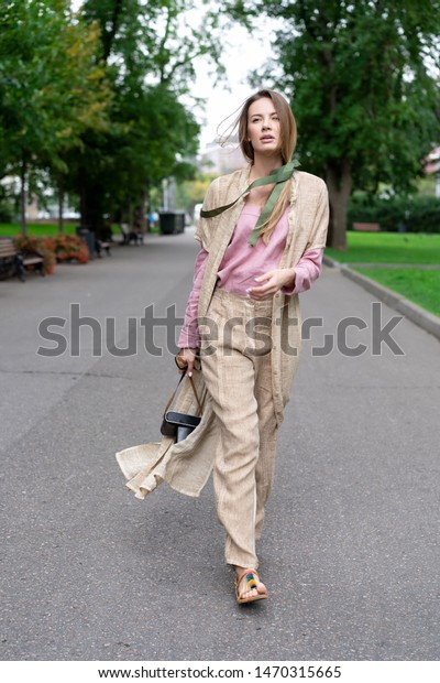 young European girl, natural appearance, long hair, beautiful face, coffee colored trousers and jacket, pink shirt is fun to walk on pavement city park. Comfortable linen womens clothing.