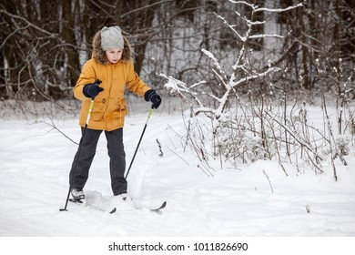 Young European girl running on ski in winter forest, full-length, copyspace