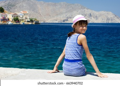 Young European girl  teenager smiling on the background of the sea,boats and houses