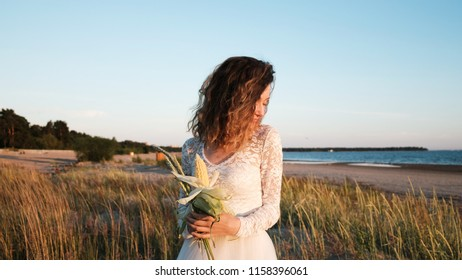 Young European girl in a wedding dress is standing in the grass with a bouquet of bride handmade of grass and corn by the sea at sunset in the summer.
