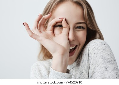 Young European joyful blonde female looking at camera through fingers in OK-gesture. Woman in casual clothes, smiling broadly. Her happy face expression proves everything goes according to plan.
