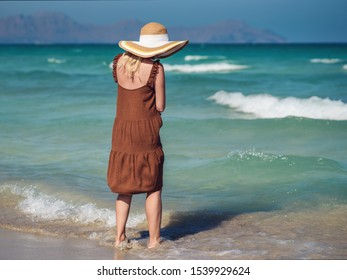 Young European lady in colorful bonnet hat and beautiful dress walking along picturesque wavy sea, she enjoying serenity around.