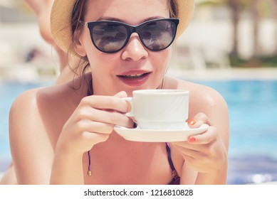 Young European lady in a sunhat is laying at the sunbed near the pool. She is enjoying her holidays and holding a cup of coffee in her hands.