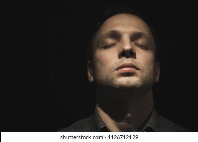 Young European man with closed eyes over black background, low key studio photo