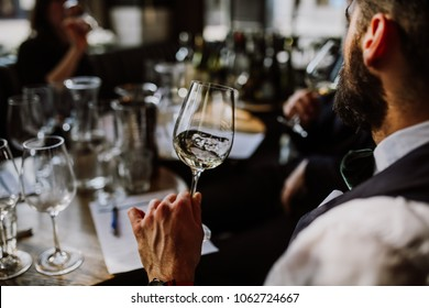 A young European man drinking white wine at the wine tasting. Selective focus point on the wine glass and the man. Other glasses and wine bottles in the background.