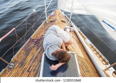 young european man having a nausea seasickness. He is trying to stop vomiting. Travelling on old boat with sail