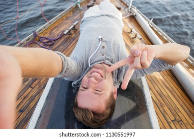 young european man making selphie on yacht. Travelling on old boat with sail