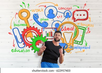 Young european man pointing up on wooden background with business sketch. Communication concept