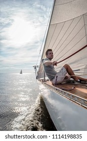 young european man sitting at edge of yacht looking at sea. Travelling on old boat with sail