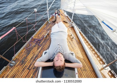 young european man sitting on yacht looking at sea. Travelling on old boat with sail. Concept of free lifestyle