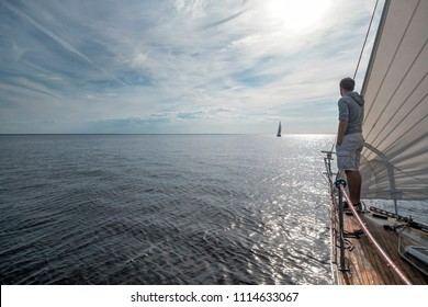 young european man standing at edge of yacht looking at sea. Travelling on old boat with sail. Luxury lifestyle