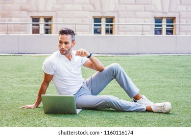 Young European Man studying, working in New York City, with beard, little gray hair, wearing white Polo shirt, gray pants, white sneakers, sitting on green lawn, working on laptop computer, thinking.