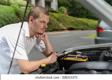 Young european man is thinking about what is wrong with his car