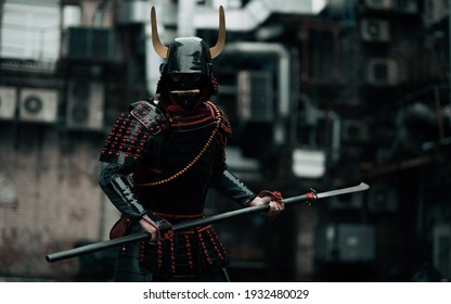 A young European man in a traditional Japanese samurai ronin costume with a katana sword on a dark background and on the street. Cosplay and Carnival