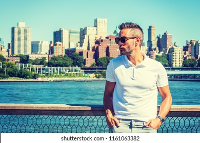 Young European Man traveling in New York, with beard, little gray hair, wearing white Polo shirt, sunglasses, standing by East River, looking around, thinking. Brooklyn buildings on far background.