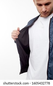 Young european man in white sweater and black pants, blue bomber jacket posing on white background. Isolated.