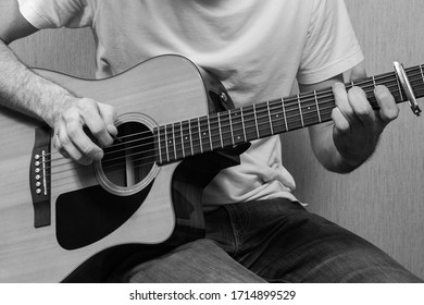 A young European man without a face with jeans and a white T-shirt plays on an acoustic guitar. Black and white photo.