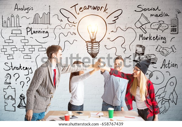 Young european team members hi-fiving each other above wooden desk. Brick wall with business sketch in the background. Teamwork concept