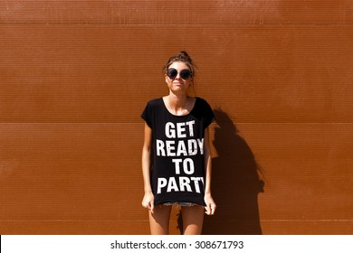 Young European teenage brunette curly model posing near brown ribbed wall, grimacing, jumping, wearing blue jeans mini shorts, sneakers, round sunglasses and black t-shirt, ready to party