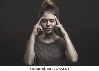 Young european woman having headache, feeling tired or ill, holding fingers on her temples. Monochrome shot of stressed female trying to relax or peace her mind, making head massage