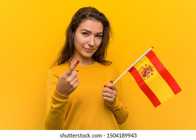 Young european woman holding a spanish flag pointing with finger at you as if inviting come closer.
