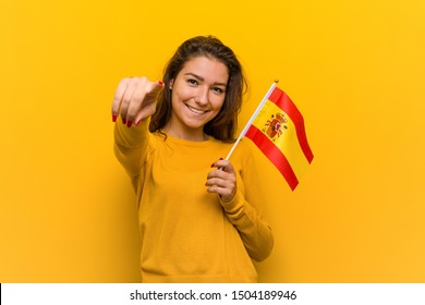 Young european woman holding a spanish flag cheerful smiles pointing to front.