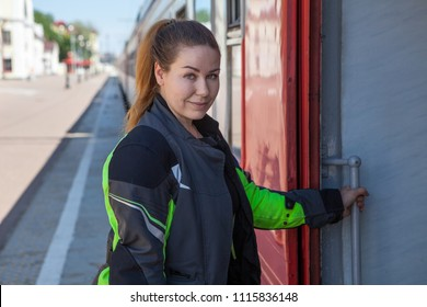 Young European woman portrait while entering train on railroad station, dressed motorcycle jacket
