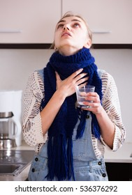 Young european woman in scarf gargling throat with domestic soda