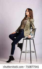 Young European woman showing different poses while sitting on a stool. Beautiful girl in jeans, tiger blouse and  jacket sitting on a bar stool