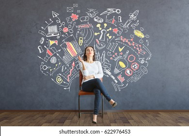 Young european woman sitting on chair and daydreaming about success in interior with business sketch