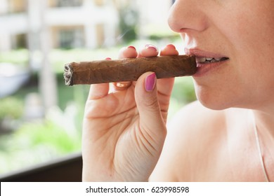 Young European woman smokes handmade cigar, closeup photo with selective focus. Dominican Republic