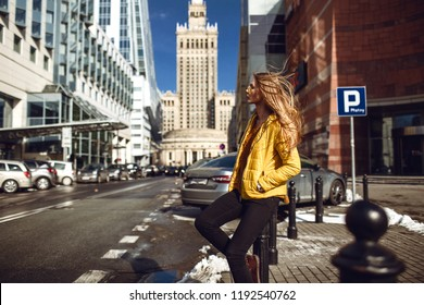 A young European woman, traveling, with long blond hair, wearing a yellow jacket, yellow sunglasses walking down the city center street, street shooting. Even light.