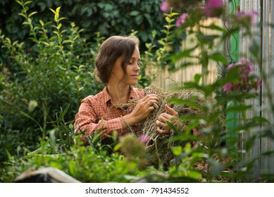 Young european woman working in garden with flowers and green plants. Summer bright day. Permaculture concept.