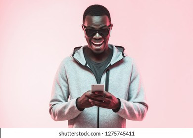Young excited african american man looking at his phone with surprise expression and mouth wide open, isolated on pink background