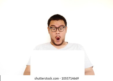 Young excited asian man with wow face holding laptop on his lap isolated on white background