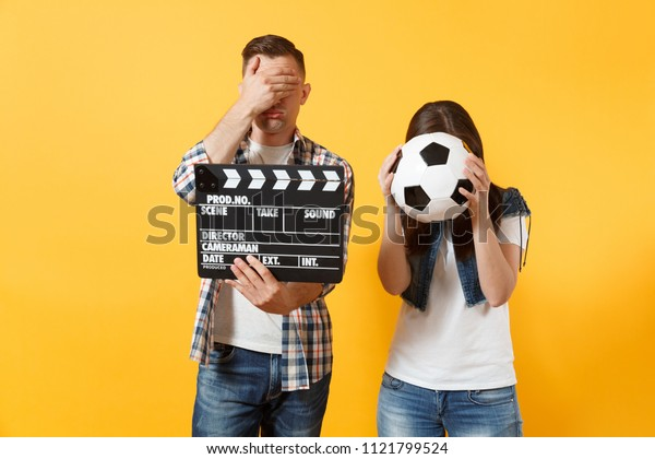 Young excited couple woman man football fans cheer up support team with soccer ball, film making clapperboard isolated on yellow background. Sport family leisure lifestyle concept. Cameraman studio