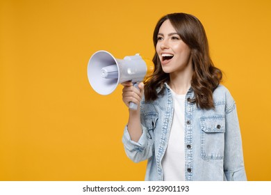 Young excited expressive brunette fun woman 20s wearing casual denim shirt white t-shirt screaming hot news shouting aside in megaphone hurry up isolated on yellow color background studio portrait.