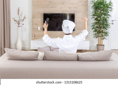 young excited happy woman watching a television