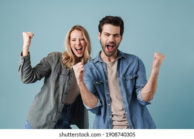 Young excited man and woman screaming and making winner gesture isolated over blue background - Shutterstock ID 1908740305