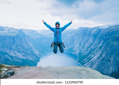 Young excited sporty woman hiker in blue jacket jumping on Norway mountain plateau. Scenic fjord on background, Norway.