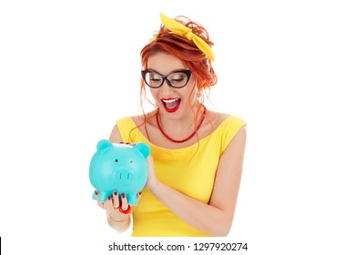 Young excited woman holding looking down euphoric amazed stunned at a piggy bank. Caucasian person in yellow dress and coral necklace with red lipstick redhead hair isolated on white studio background