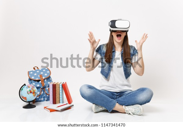 Young excited woman student wearing virtual reality glasses spreading hands enjoying sitting near globe, backpack, school books isolated on white background. Education in school university college