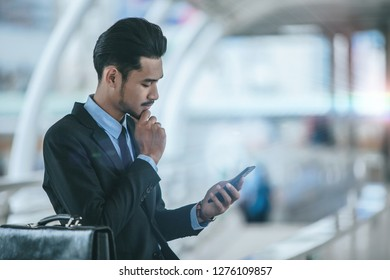 Young executive businessman using a mobile phone at the airport terminal
