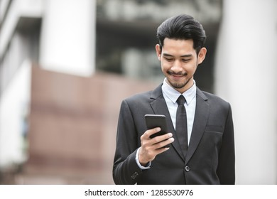 Young executive businessman using a mobile phone in the business district with skyscrapers buildings background