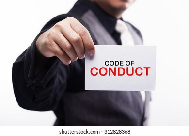 young executive holding card written code of conduct